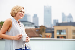 Young Woman Relaxing On Roof Terrace With Cup Of Coffee Royalty Free Stock Photos