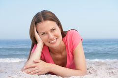 Young Woman Relaxing On Sandy Beach. Smiling At Camera Stock Photos