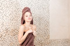 Young woman relaxing in a sauna dressed in a towel. Interior of new Finnish sauna, infrared panels for medical. Procedures, classic wooden sauna Stock Image