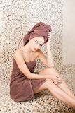 Young woman relaxing in a sauna dressed in a towel. Interior of new Finnish sauna, infrared panels for medical. Procedures, classic wooden sauna Stock Photos