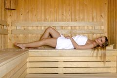 Young woman relaxing in sauna and enjoy the hot air. Royalty Free Stock Images