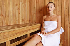 Young woman relaxing in sauna. Young woman relaxing in a sauna in her holidays Royalty Free Stock Photo