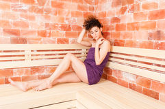 Young woman relaxing in sauna room and wearing towel. As calm and wellbeing concept Stock Image