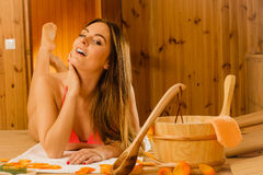 Young woman relaxing in sauna. Spa wellbeing. Young woman with bucket ladle and petals relaxing laying in wood finnish sauna. Attractive girl in bikini resting Royalty Free Stock Photo