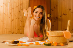 Young woman relaxing in sauna. Spa wellbeing. Young woman with bucket ladle and petals relaxing laying in wood finnish sauna. Attractive girl in bikini resting Stock Photo