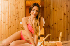 Young woman relaxing in sauna. Spa wellbeing. Young woman with bucket ladle and petals relaxing in wood finnish sauna. Attractive girl in bikini resting. Spa Royalty Free Stock Images