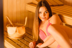 Young woman relaxing in sauna. Spa wellbeing. Young woman with bucket and ladle relaxing in wood finnish sauna. Attractive girl in bikini resting. Spa wellbeing Royalty Free Stock Photo