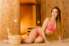 Young woman relaxing in sauna. Spa wellbeing. Young woman with bucket and ladle relaxing in wood finnish sauna. Attractive girl in bikini resting. Spa wellbeing Stock Image