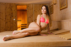 Young woman relaxing in sauna. Spa wellbeing. Young woman relaxing in wooden finnish sauna. Attractive girl in bikini resting. Spa wellbeing pleasure Stock Photos