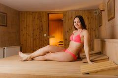 Young woman relaxing in sauna. Spa wellbeing. Young woman relaxing in wooden finnish sauna. Attractive girl in bikini resting. Spa wellbeing pleasure Stock Image