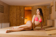 Young woman relaxing in sauna. Spa wellbeing. Royalty Free Stock Image
