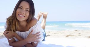 Young woman relaxing in the shade of an umbrella. Happy young woman relaxing in the shade of an umbrella on the beach lying facing the camera with a lovely stock video footage