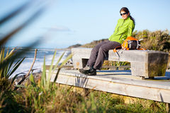 Young woman relaxing. Young woman sitting on a bench on a seashore Stock Photo