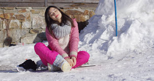 Young woman relaxing on skiing holiday. Full body portrait of young woman in pink snowsuit sat on snow relaxing on skiing holiday with eyes closed royalty free stock photo