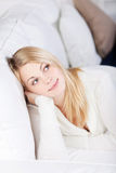 Young Woman Relaxing And Smiling At Home on Sofa Royalty Free Stock Photos