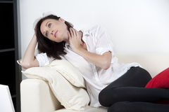 Young woman relaxing on sofa Stock Images