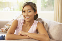Young Woman Relaxing On Sofa At Home Stock Photo