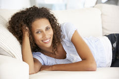 Young Woman Relaxing On Sofa At Home Royalty Free Stock Image