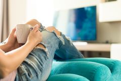 Young woman relaxing on the sofa at home, watching tv and enjoying coffee. Beautiful young woman relaxing on the sofa at home, watching tv and enjoying coffee Stock Image