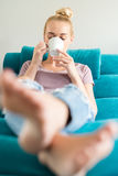 Young woman relaxing on the sofa at home, watching tv and enjoying coffee royalty free stock images