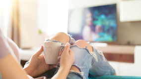 Young woman relaxing on the sofa at home, watching tv and enjoying coffee, top view. Beautiful young woman relaxing on the sofa at home, watching tv and enjoying royalty free stock images