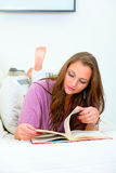 Young woman relaxing on sofa and reading book Stock Photos