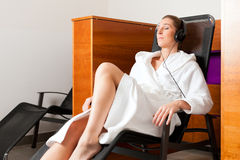 Young woman relaxing in spa with music Stock Photo