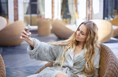 Young woman relaxing in the spa resort doing selfy Stock Photography