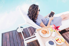 Young woman relaxing on a sun lounger near poolside Stock Images
