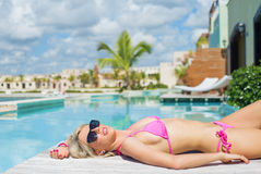 Young woman relaxing and sunbathing on the deck by the pool stock photos