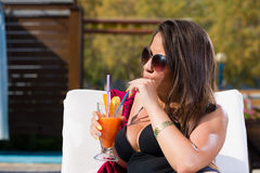 Young woman relaxing by the swimming pool. Enjoying her fresh cocktail Royalty Free Stock Photo