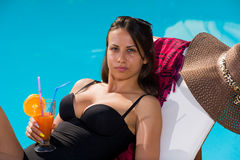 Young woman relaxing by the swimming pool. Enjoying her fresh cocktail Royalty Free Stock Photography