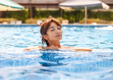 Young woman relaxing in a swimming pool stock photos