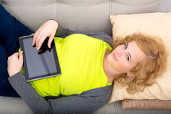 Young woman relaxing with a Tablet PC on the Sofa Royalty Free Stock Image