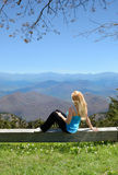 Young woman relaxing on the top of the mountain. Stock Images