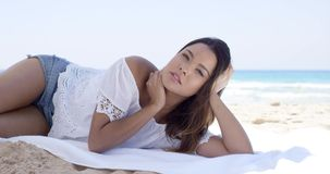 Young woman relaxing on a towel on the beach. Attractive young woman relaxing on a towel on the beach in a trendy summer outfit in the shade of a beach umbrella stock video