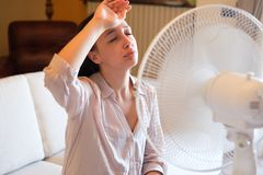Woman feeling hot and trying to refresh in summertime heat. Young woman relaxing under the air fan at home Royalty Free Stock Image
