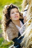 Young woman relaxing under a hay stack in autumn Stock Photos