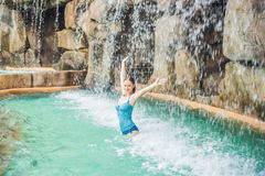 Young woman relaxing under a waterfall in aquapark Royalty Free Stock Photo