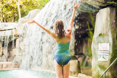 Young woman relaxing under a waterfall in aquapark Royalty Free Stock Photos