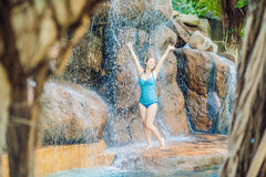 Young woman relaxing under a waterfall in aquapark Stock Photo