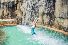 Young woman relaxing under a waterfall in aquapark Stock Photos