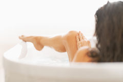 Young woman relaxing washing in bathtub. rear view Royalty Free Stock Photos