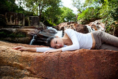 Young woman relaxing by the waterfall Stock Images