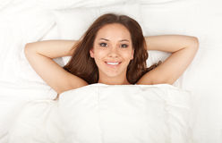 Young woman relaxing in white bedding Stock Photos