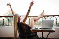Young woman with raised hands relaxing with laptop computer on a balcony on summer vocation. Young woman relaxing with a white modern laptop computer on a Royalty Free Stock Photos