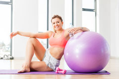 Young woman relaxing after workout. Young woman relaxing after fitness workout. Cheerful sportswoman sitting next to a fitball. Healthy lifestyle stock photos