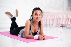 Young woman relaxing after workout at home lying Stock Photography