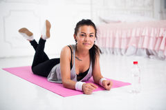 Young woman relaxing after workout at home lying. On yoga mat concept healthy lifestyle, training, diet stock images