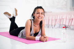 Young woman relaxing after workout at home lying Stock Photo